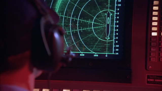 medium angle, sonar display with missile launch graphics and activity on screen. operator in front of screen. see collision alert flash on screen as missiles move from left and hit submarine target at right. - 潜水艦点の映像素材/bロール
