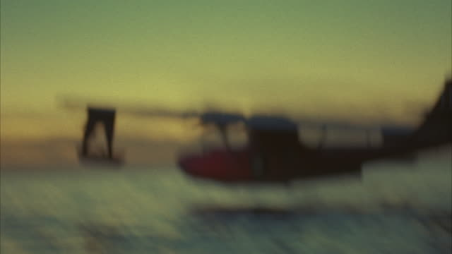wide angle of small dual propeller red airplane taking off or performing take-off in ocean or sea at dusk. - isole del pacifico video stock e b–roll