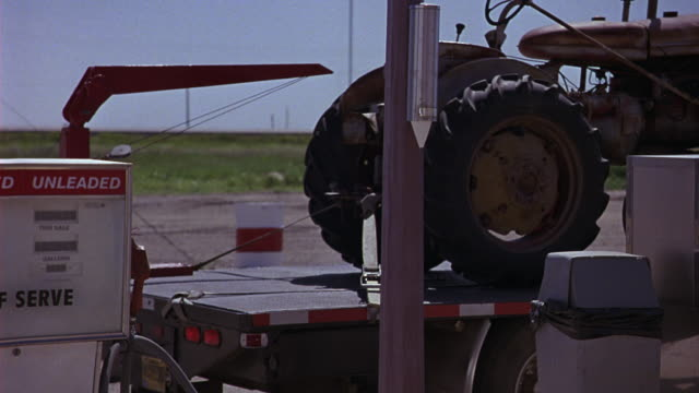 medium angle of a tractor on a trailer at a country gas station. large tractor tires. old fashioned gas pump in foreground. country road and countryside in background. - agricultural equipment stock videos and b-roll footage