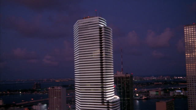 AERIAL OF MIAMI SKYLINE AND FOCUSES AND ROTATES AROUND BANK OF AMERICA TOWER. SKY HAS GRAY CLOUDS.