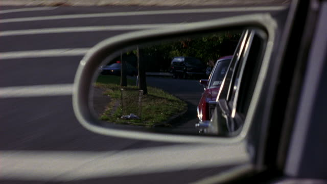 medium angle of left side mirror of silver of white car. see red 1981 chrysler fifth avenue in mirror. see car swerve as fifth avenue follows. looks like car chase. chrysler car. - stunt stock-videos und b-roll-filmmaterial