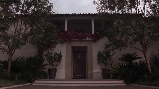pan down, pan up of art deco or spanish style two story house with lots of plants, trees along driveway. overcast day. series. upper class. - zweistöckiges wohnhaus stock-videos und b-roll-filmmaterial