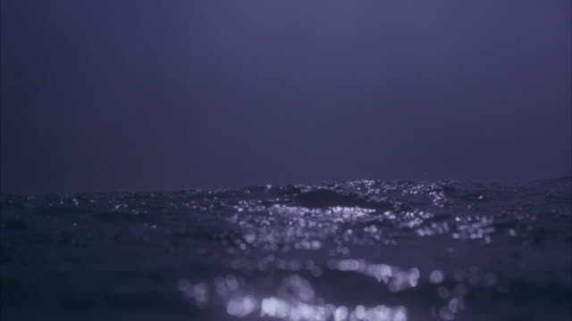 MEDIUM ANGLE OF OCEAN WAVES AT NIGHT. POV RIGHT AT SURFACE OF WATER. SEE MIST OR FOG. BOAT OR SHIP SUDDENLY EMERGES OUT OF WATER, THEN FLOATS IN OCEAN. CAMERA BRIEFLY GOES PARTIALLY UNDERWATER, IS SUBMERGED.