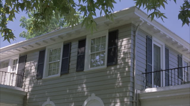 stockvideo's en b-roll-footage met medium angle of second story of front of house. see two windows at center and a balcony on either side. see overhanging tree at top. upper class. - rotsmuur