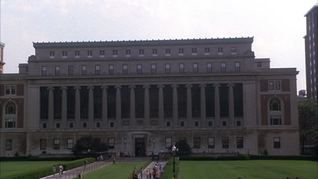 EST WIDE ANGLE ON A BUILDING AT COLUMBIA UNIVERSITY. BRICK BUILDING CONTAINS NUMEROUS COLUMNS WITH GRASS LAWN IN FRONT OF BUILDING. SEE STUDENTS WALKING AROUND AND SITTING ON LAWN.