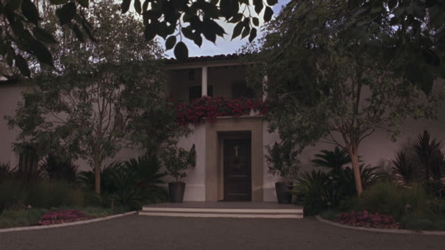 medium angle of art deco or spanish style two story house with lots of plants, trees along driveway. windy day, branches swaying. upper class. - https stock videos & royalty-free footage