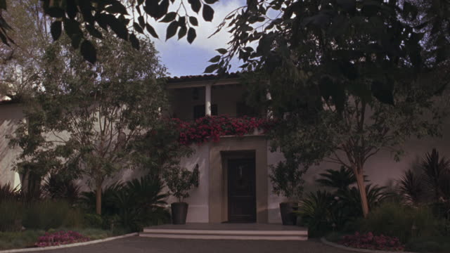 medium angle of art deco or spanish style two story house with lots of plants, trees along driveway. windy day, branches swaying. upper class. - zweistöckiges wohnhaus stock-videos und b-roll-filmmaterial