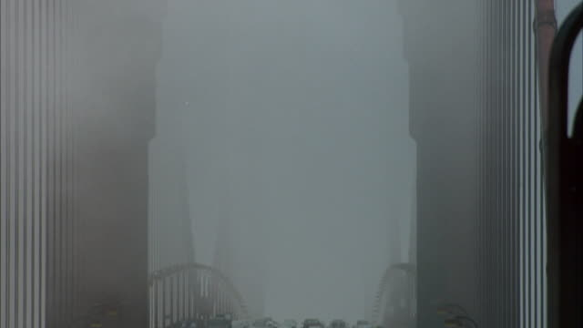 pan down from blue sky to fog shrouded deck of golden gate bridge. see traffic and red volkswagen karmann ghia car approach front and exits frame to right. see people on bridge sidewalk. - fog stock videos & royalty-free footage