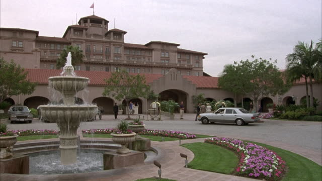 vidéos et rushes de wide angle of hotel or upper class resort. fountain in left foreground, white mercedes pulls around circle driveway. some people wait outside with luggage carts. location is huntington hotel in pasadena. - stéréotype de la classe supérieure