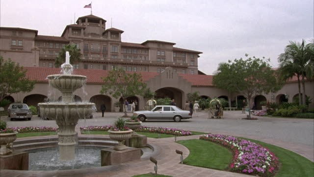 vidéos et rushes de wide angle of hotel or upper class resort. fountain in left foreground, white mercedes pulls around circle driveway. some people wait outside with luggage carts. - stéréotype de la classe supérieure