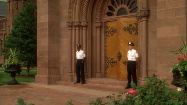 medium angle of two guards standing on either side of two ornate wood doors of a brown brick palace. see a young woman in a white skirt and black blouse - 黒のシャツ点の映像素材/bロール