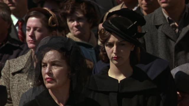 close angle of crowd of mourners at funeral. men, women in period costume. louisiana state capitol building in background. flowers. - funeral stock videos & royalty-free footage
