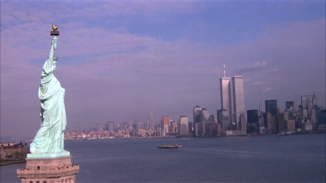 aerial of statue of liberty and upper new york bay in front of manhattan with new york city skyline. world trade center, twin towers. pulls back from statue of liberty to see more of skyline. - 1990 stock videos & royalty-free footage