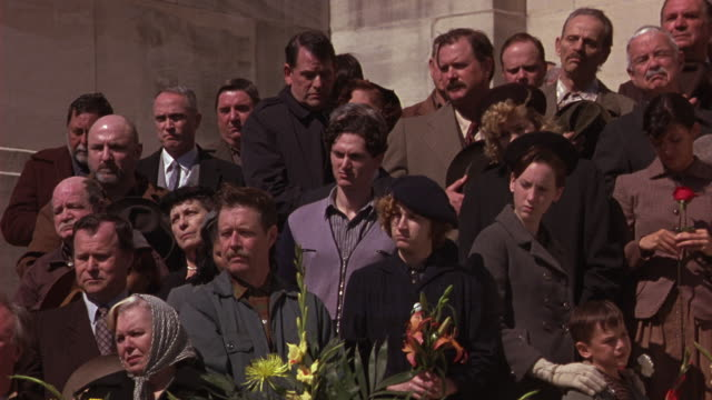 wide angle of crowd of mourners at funeral. men, women in period costume. louisiana state capitol building in background. flowers. - kapitol von louisiana stock-videos und b-roll-filmmaterial