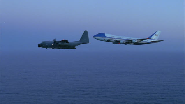 AERIAL OF AIR FORCE ONE JET AND C-130 HERCULES PLANE FLYING ACROSS SCREEN FROM RIGHT TO LEFT. VIEW OF AIR FORCE ONE PARTIALLY BLOCKED BY C-130. AT END AIR FORCE ONE FLIES OFF SCREEN TO BOTTOM.