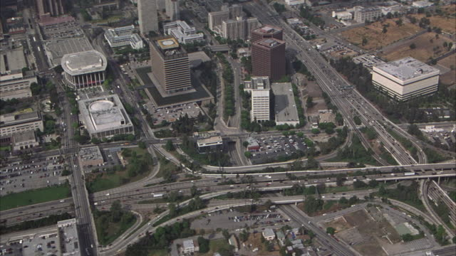 AERIAL THAT PANS DOWN FROM SMOGGY SKY TO LOS ANGELES DOWNTOWN, THEN PANS DOWN TO INTERCHANGE OF I-101 (HOLLYWOOD FREEWAY) AND I-110 (HARBOR FREEWAY), ZOOMS IN CLOSER TO FREEWAY OR HIGHWAY.