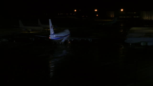 MEDIUM ANGLE OF AIR FORCE ONE BOEING 747 JET PARKED ON RUNWAY OF AIRPORT. SEVERAL OTHER PARKED JETS VISIBLE AS WELL.