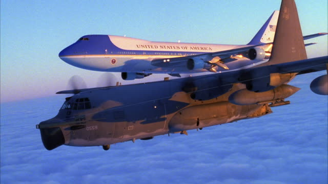 TRACKING SHOT OF AIR FORCE ONE JET AND C-130 HERCULES AIRPLANE FLYING ABOVE CLOUD COVER AND ACROSS SCREEN FROM RIGHT TO LEFT.