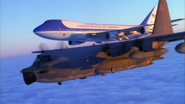 TRACKING SHOT OF AIR FORCE ONE JET AND C-130 HERCULES AIRPLANE FLYING ABOVE CLOUD COVER AND ACROSS SCREEN FROM LEFT TO RIGHT.