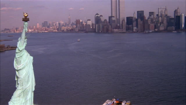 vídeos de stock e filmes b-roll de aerial of statue of liberty and new york city skyline with upper new york bay. pans up statue of liberty and moves right past torch. world trade center twin towers. - statue of liberty new york city