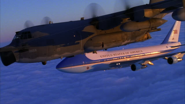 TRACKING SHOT OF AIR FORCE ONE JET AND C-130 HERCULES FLYING ACROSS SCREEN FROM RIGHT TO LEFT ABOVE CLOUD COVER.