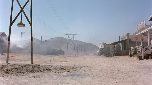 vidéos et rushes de medium angle of dusty road of deserted western town. see dust blowing in the wind outside of buildings. see mountains in the background. - ouest américain
