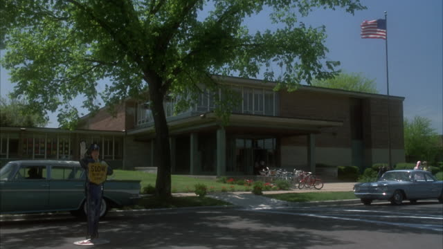stockvideo's en b-roll-footage met medium angle of school with classic cars parked in front including a chevrolet corvair. children run out of door, probably when school is out, could be for summer vacation. american flag on flagpole lowered by student. neg cut. - school building