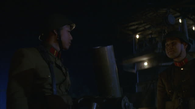 medium angle of two north korean soldiers dressed in olive green uniforms and helmets. soldiers insert shell into mortar gun and appear fire the weapon. gray guard tower visible  in background. combat. military bases. - mortar weapon stock videos & royalty-free footage