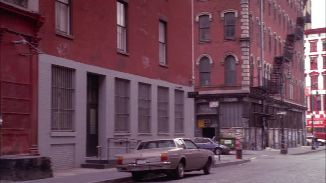 wide angle of lower manhattan neighborhood street lined with multi-story brick apartment buildings. storefronts visible at end of street. - tribeca stock videos & royalty-free footage