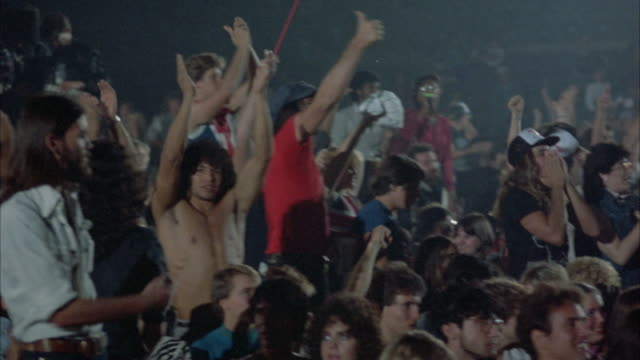 MEDIUM SHOT. ROCK CONCERT AUDIENCE (YOUNG AND DRESSED IN EARLY 1980'S ATTIRE). CROWD SHOUTS AT STAGE, CLAPS THEIR HANDS AND RAISES THEIR ARMS AS THEY WATCH CONCERT.