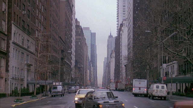 vídeos de stock, filmes e b-roll de wide angle of city street in new york city. apartment buildings on sides of street. taxis approach front and turn right. - 1980 1989