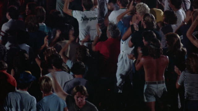 PAN RIGHT OF YOUNG AUDIENCE IN EARLY 1980'S ATTIRE, STANDING AND WATCHING ROCK CONCERT. CROWD HAS ARMS RAISED IN THE AIR, CLAPPING AND PUMPING THE AIR. SOME DANCE. PAN BACK LEFT, STOP BRIEFLY ON VARIOUS GROUPS IN THE AUDIENCE.