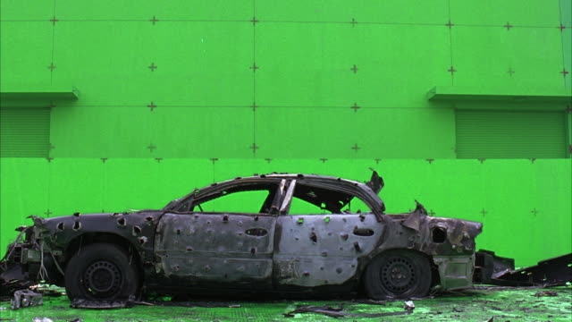 MEDIUM ANGLE OF BLACK CAR IN FRONT OF GREEN SCREEN. CAR COULD HAVE BEEN CAUGHT ON FIRE. SEE HOLES ON SIDE OF CAR. COULD BE BULLET HOLES. SEE CAR WITH NO WINDOWS OR GAS COVER. SEE FLAT TIRES. COULD BE FUTURISTIC DESIGN.