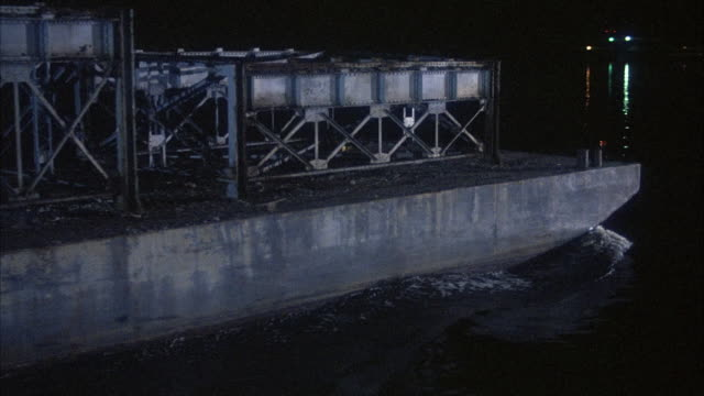 medium angle of barge with empty cargo racks passing by in body of water from left to right. possibly river, lake or ocean. see lights in distance from other boats or from land. - other stock videos & royalty-free footage