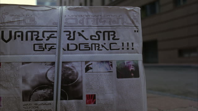 wide angle of streets or alley. see bound stack of newspapers with asian or other language in headlines and photos on front page. stack rolls away backwards. see high rise buildings in background. see closed doors and windows on building frame right. - newspaper page stock videos and b-roll footage