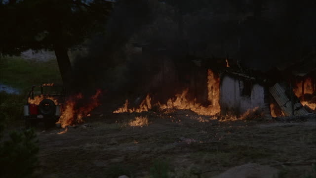 medium angle of shack or hut and red jeep burning in fire. dark gray smoke and flames. - hut stock-videos und b-roll-filmmaterial