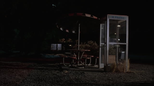 WIDE ANGLE OF PHONE BOOTH AND PICNIC TABLE. PHONE AND PHONE BOOK ARE SWINGING IN BOOTH. PICNIC TABLE HAS UMBRELLA OVER IT. GROUND IS GRAVEL. WEEDS AND BUSH AROUND PHONE BOOTH AND TABLE. LIT WINDOW IN BG. RURAL AREA. COULD BE USED FOR ROADSIDE REST AREA.
