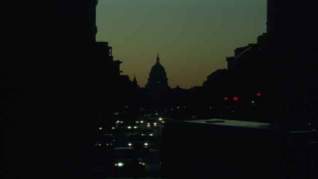 MEDIUM ANGLE OF CAPITOL BUILDING AT DUSK. SEE SILHOUETTE OF OTHER BUILDINGS, SKY HAS TINT OF LIGHT BLUE AND ORANGE. TRAFFIC ON CITY STREET IN FOREGROUND.