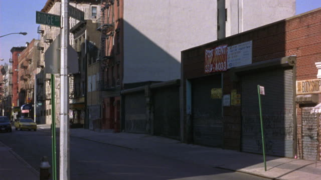 medium angle of ridge street and stanton street intersection in the lower east side, manhattan. see brick garages or storage buildings at right with for rent signs. could be residential area. - one way stock videos and b-roll footage
