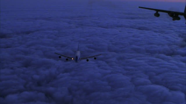 MEDIUM ANGLE OF AIR FORCE ONE JET FLYING TOWARD CAMERA ABOVE CLOUD COVER. C-130 HERCULES AIRPLANE ENTERS SCREEN FROM RIGHT AND FLIES TOWARD CAMERA AS WELL.