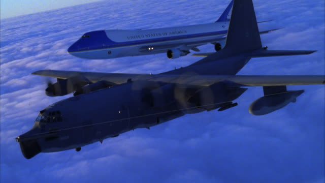 TRACKING SHOT OF AIR FORCE ONE JET AND C-130 HERCULES AIRPLANE FLYING ABOVE CLOUD COVER AND ACROSS SCREEN FROM RIGHT TO LEFT
