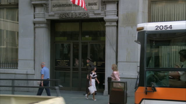 medium angle of people walking in front of the entrance to the downtown federal bank.  orange and white metro bus at right. bus drives past entrance. - 1980 1989 stock-videos und b-roll-filmmaterial
