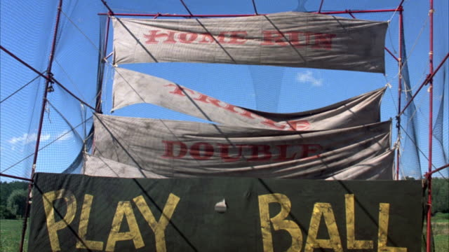 medium angle of carnival baseball game with hanging banners. banners read home run, triple, double and single with baseballs hitting each. bottom sign says play ball. fence encloses both sides of banners. could be batting cage. - gabbia di battuta video stock e b–roll
