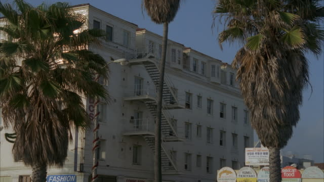 zoom in of apartment building on strand at beach. palm trees in front. staircase on side of building. venice beach. - venice beach stock videos & royalty-free footage