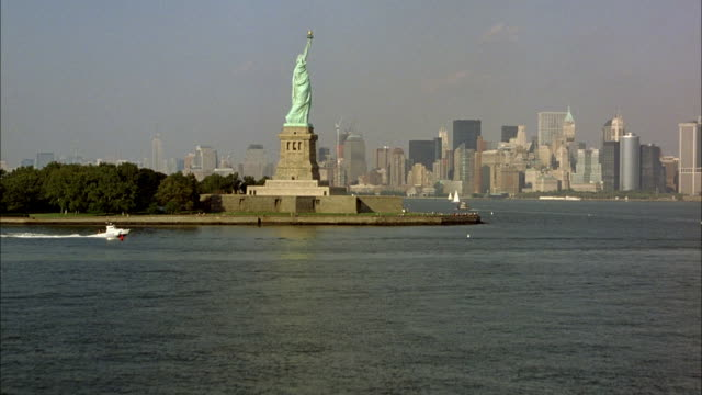 aerial over water, around statue of liberty and of new york city skyline. circles around statue to see new york city skyline in background and see boats moving through bay. - statue of liberty new york city stock videos & royalty-free footage