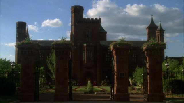MEDIUM ANGLE ESTABLISH OF SMITHSONIAN INSTITUTION. SEE FOUR FREE STANDING BRICK PILLARS IN FOREGROUND WITH PLANTS ON TOP. SEE GUARDS IN FRONT OF SMITHSONIAN INSTITUTION. SEE BLUE SKY WITH CLOUDS ON RIGHT.