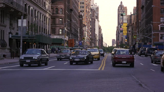MEDIUM ANGLE OF TRAFFIC ON NEW YORK CITY STREET INTERSECTION. SEE WHITE 1987 BUICK LESABRE DRIVE TOWARDS POV, CHANGE LANES, DRIVE ON THE WRONG SIDE OF THE YELLOW LINE, TURN RIGHT TO CUT OFF ONCOMING TRAFFIC, AND EXIT SPEEDING TO BACKGROUND.