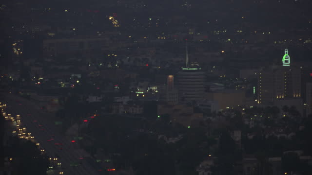 pan up of city highway with cars in light traffic to multi-story buildings. capitol records building and the knickerbocker hotel visible. hollywood on right. series. - capitol records stock-videos und b-roll-filmmaterial