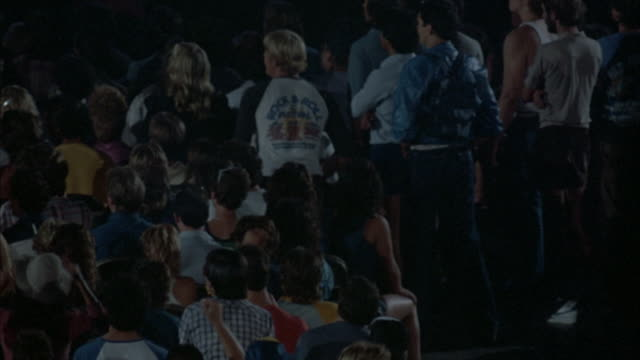 MEDIUM ANGLE. PAN L-R OF ROCK CONCERT. YOUNG AUDIENCE DRESSED IN EARLY 1980'S ATTIRE SHOWN FROM BEHIND. CROWD SHOWN SEATED AND SWAYING TO MUSIC, THEN THEY STAND AND RAISE THEIR ARMS IN THE AIR