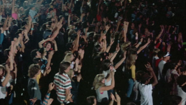 SHOT BEGINS WITH A PAN, RIGHT TO LEFT, ACROSS A ROCK CONCERT AUDIENCE (YOUNG AND DRESSED IN EARLY 1980'S ATTIRE). THE CROWD IS SEEN DANCING WITH ARMS RAISED